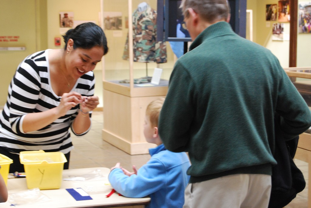 "NMUSN Curatorial Intern works with a visitor at ""Take Your Child to Work"" Day."