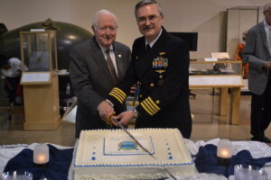 NHF Chairmain Admiral Bruce DeMars, USN (Ret.) and Captain David Ogburn, USN cut the cake.