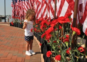 A girl places a flower beneath a row of flags during a 9/11 ceremony in Norfolk, Va. The City of Norfolk hosted an all-day healing and remembrance ceremony at Town Point Park to mark the 10th anniversary of the Sept. 11, 2001 attacks. (U.S. Navy photo by Mass Communication Specialist 3rd Class Stuart Phillips/Released)