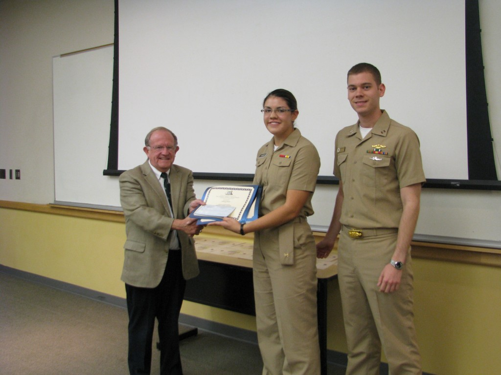 University of Idaho Dean of Students, Dr. Bruce Pittman, present MIDN Diana Vaught her award with Seapower & Maritime Affairs course instructor LT Nathan Greenwood.