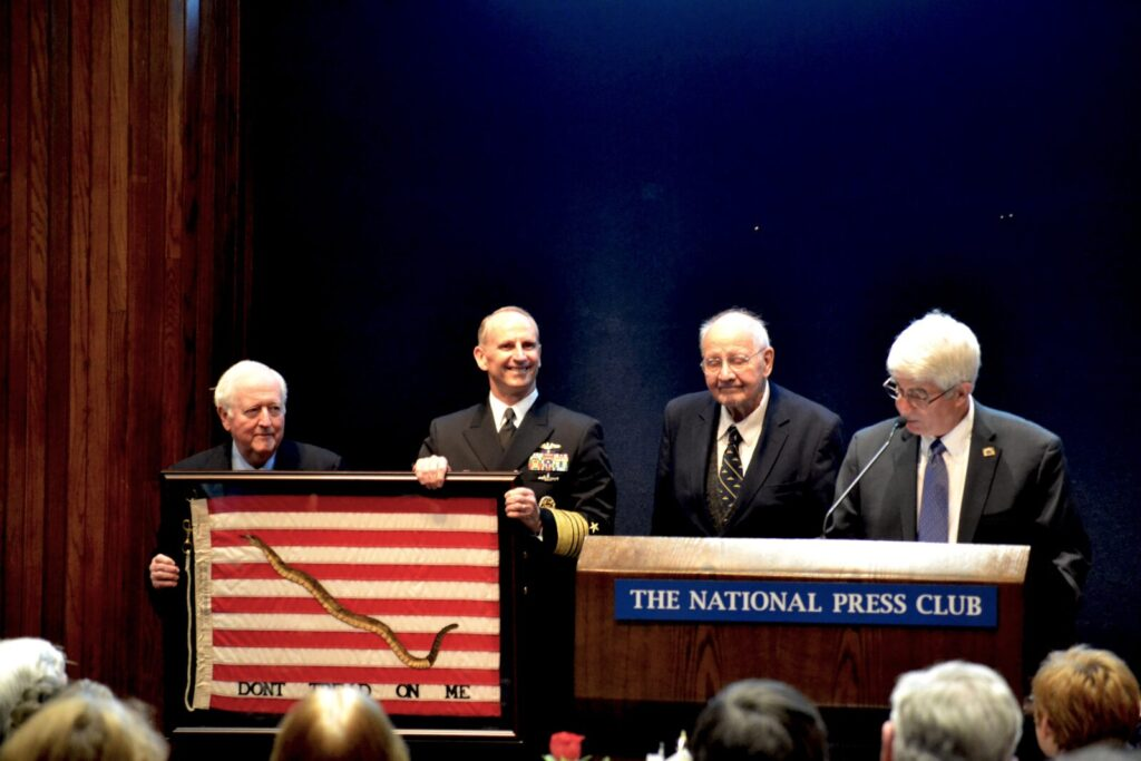 NHF Chairman Bruce DeMars, USN (Ret.) and Ambassador Middendorf present Greenert with an original 1975 Navy Jack.