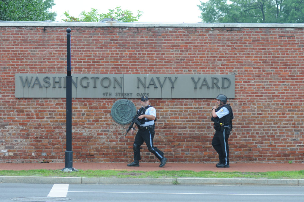 150702-N-ED767-103 WASHINGTON (July 2, 2015) Police officers walk past the Washington Navy Yard on M Street in response to a possible active shooter at the Navy Yard. (Oscar Sosa)