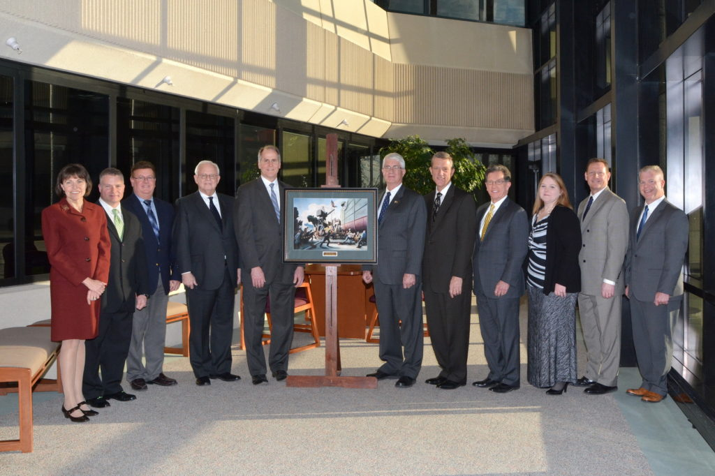 "Executive Director Captain Todd Creekman, USN (Ret.) stands with the Thomas Hart Benton print ""Cut the Line"" alongside members of the Cincinnati Insurance Company during a visit to their headquarters during his January 2016 visit. (left to right): Dawn Alcorn, Vice President, Administrative Services; Mike Weigel, Press Operator II, Printing; Roger Chamberlain, Secretary and Manager, Printing; Jack Schiff, Jr., Chairman of the Executive Committee, Cincinnati Financial Corporation; Steve Johnston, President and CEO, Cincinnati Financial Corporation; Captain Todd Creekman, USN (Ret), Executive Director, Naval Historical Foundation; Dirk Debbink, Director, Cincinnati Financial Corporation; Tim Timmel, Senior Vice President, Operations; Lori Justice, Graphic Designer II, Printing; Brian Wood, Vice President, Human Resources; and Jim Streicher, Vice President, Personal Lines Support."