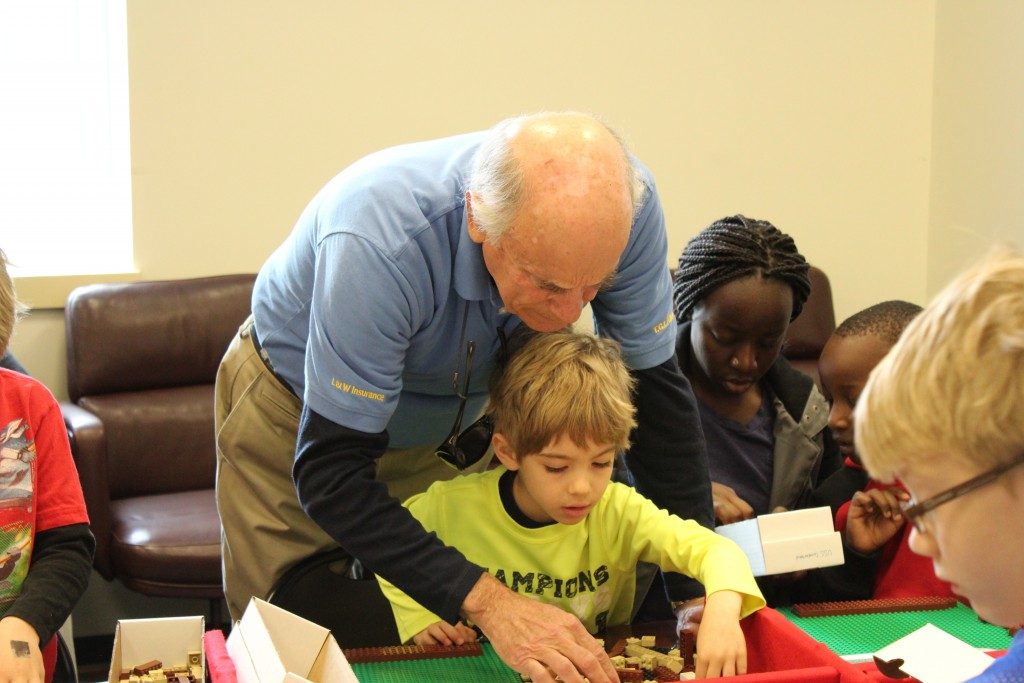 A Kalmar Nyckel volunteer works with a participant as he builds Battleship Wisconsin. (NHF Photo/Matthew Eng/Released)