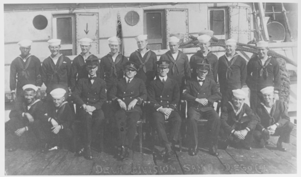 (AT-54) Deck Division posed beside the ship, at San Diego, California, circa early 1921. Seated in chairs are (from left to right): Chief Carpenter's Mate John Wesley Powell; Boatswain Harvey H. Reinbold, Executive Officer; Boatswain Roy E. Hoffses, Ordnance Officer; and Chief Boatswain's Mate Elias Melvin Zimmerman. The Sailor marked by an arrow (top row) may be Seaman 1st Class W.P. Burbage. Courtesy of W.P. Burbage, 1970. U.S. Naval History and Heritage Command Photograph. (# NH 71507)
