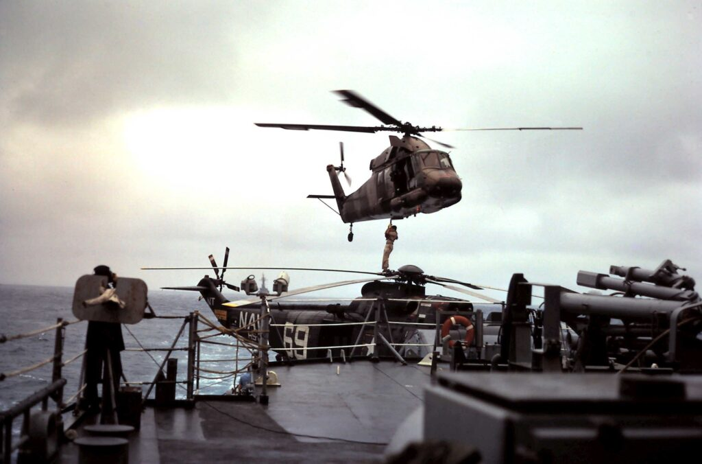 SAR operations in the Tonkin Gulf, Mar/Apr 1967 aboard the USS England (DLG 22). An SH-3 is parked on the fantail flight deck while a UH-2 picks up a traveler via sling. (NAVSOURCE)