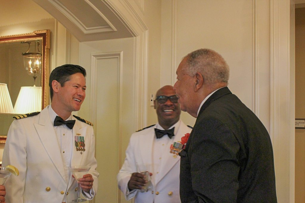 Midway veteran William Fentress entertains active duty naval officers at this year's Midway dinner (NHF Photo)