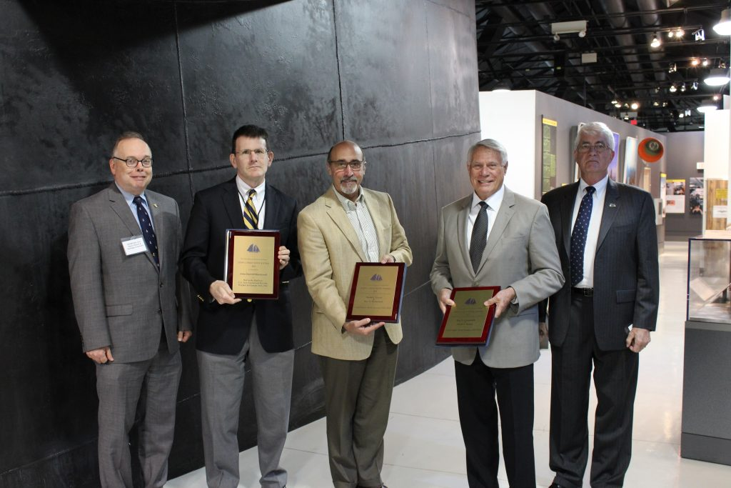 NHHC Director Admiral Sam Cox, USN (Ret.) and NHF Director Captain Todd Creekman, USN (Ret.) stand next to Naval History and Heritage Command historians who recently received the John Lyman book prize for their contributions to naval history from the North American Society for Oceanic History during a special presentations at the 2016 NHF Annual Meeting.