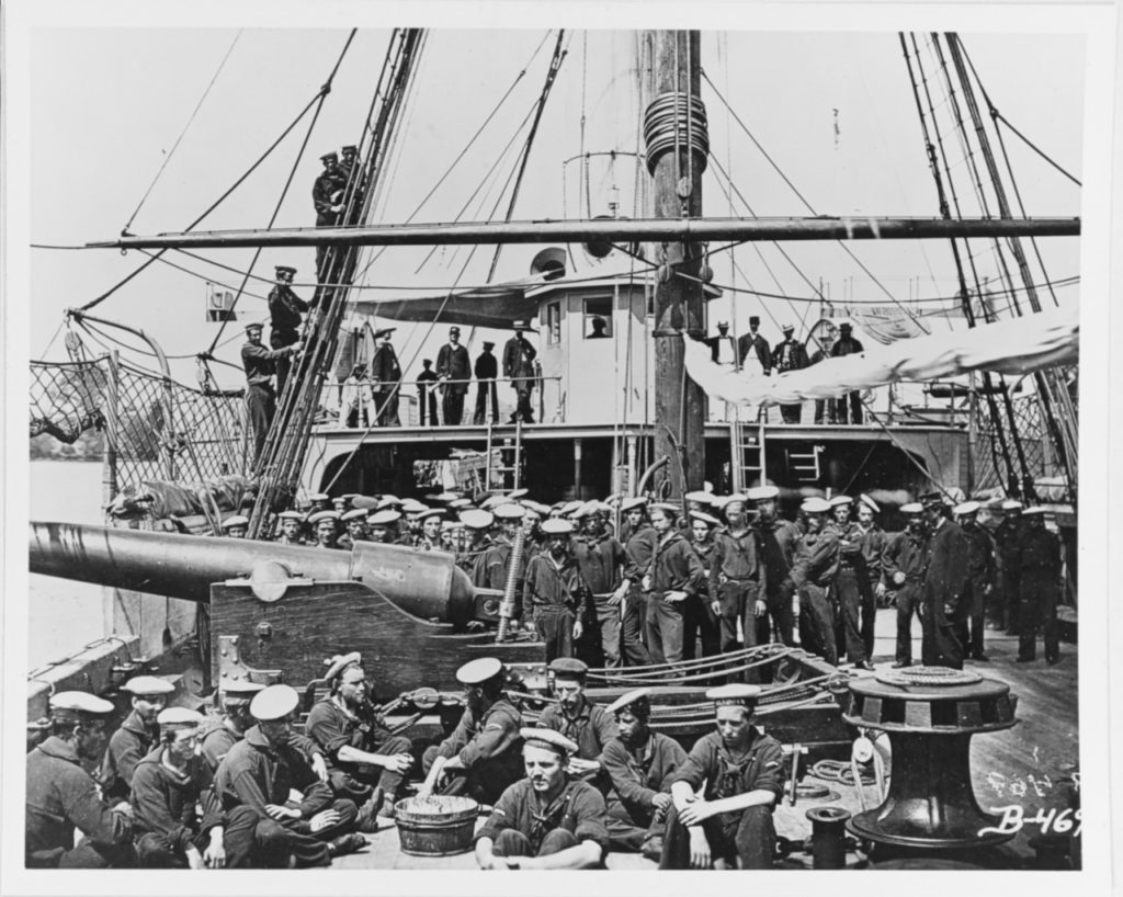 Ship's officers and crew on the foredeck, 1864-65. Photographed by Matthew Brady. Note 100-pounder Parrott rifled gun on a pivot carriage; men wearing white flat hats with the ship's name on the hat ribbon; foremast and yard; anti-boarding netting; and capstan. The original negative is # 111-B-469 in the National Archives. U.S. Naval History and Heritage Command Photograph.