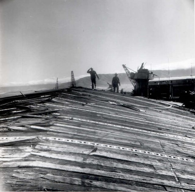 """CVL-22 flight deck damage from the """"Able"""" blast (as described above).The ships island and crane are behind and on the right side of the worker. (Photo: Scan by John G. Lambert at NARA San Bruno, CA on the 2015 Independence mission.)"""